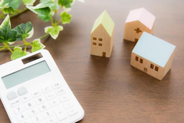 電卓と小さな家の模型