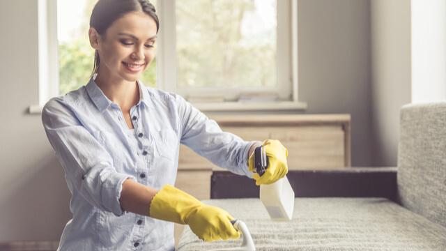 ソファの掃除をしている女性